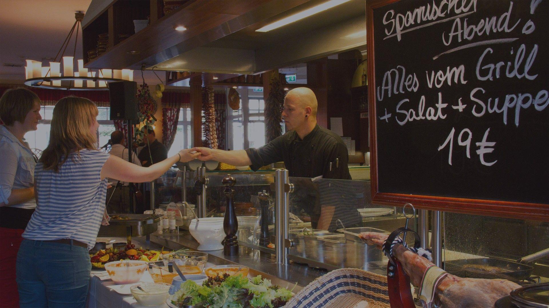 Das Bild zeigt den Innenraum des spanischen Restauramts Bodega in Wernigerode. Der Innenraum präsentiert sich im mediterranen Stil. Eine offene Theke begrüßt die Gäste den Köchen, bei der Zubereitung der Speisen über die Schulter zu schauen.