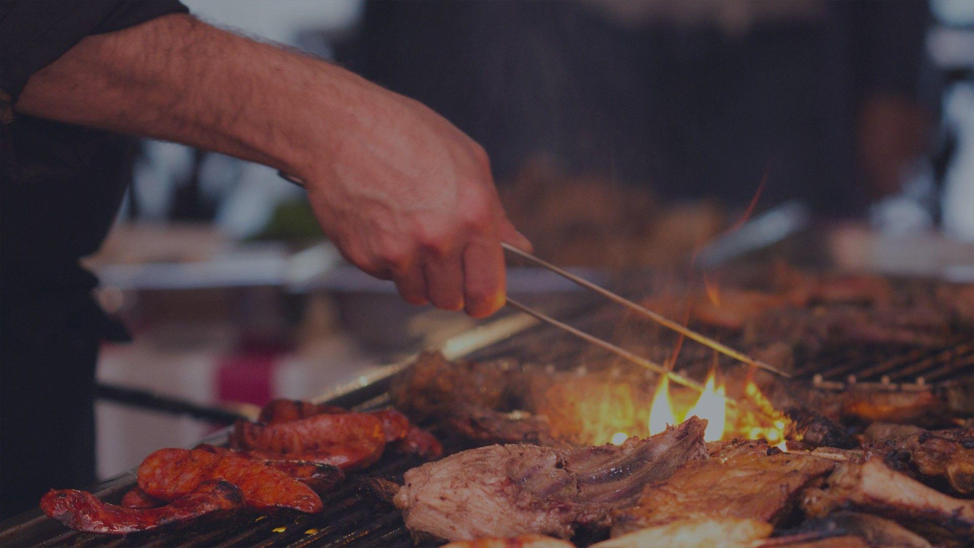 Zu sehen ist ein Grillabend in der Bodega, dem spanischen Restaurant in Wernigerode. Einer der Köche wendet das Fleisch.